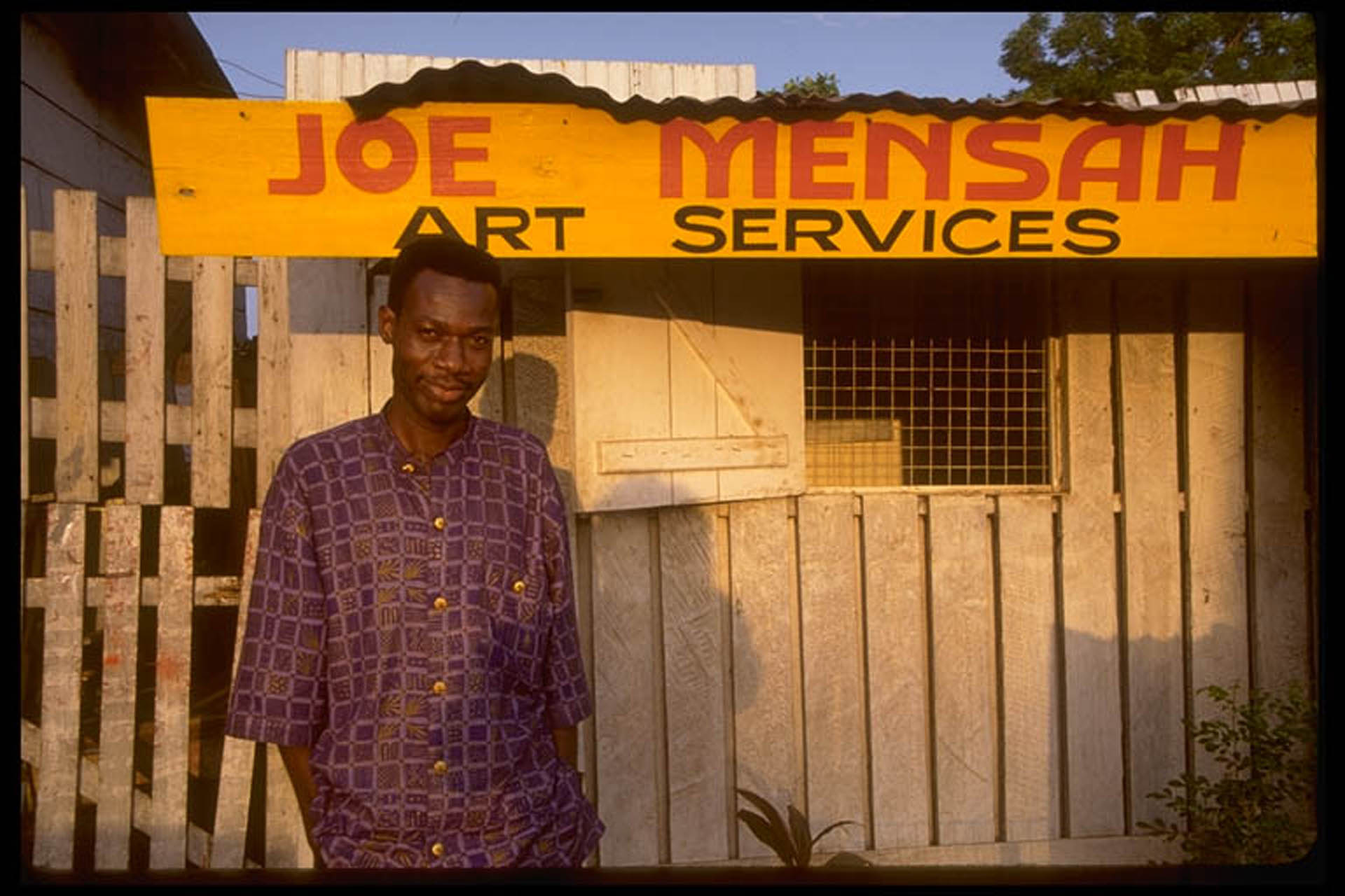 Joe Mensah in front of Joe Mensah Art Services, 1998